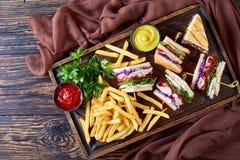 Knapperige sandwiches en gebraden gerechten op een dienende raad stock foto