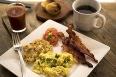 Knaprig bacon och fluffiga förvanskade ägg Fotografering för Bildbyråer