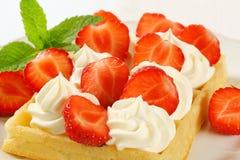Knaprig dillande med jordgubbar och kräm Arkivfoton