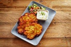 Knapriga Fried Potato Rosti Served med sallad och doppet royaltyfri foto