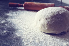 Knead flour toned dough. Food crumbly dough from flour on the chef`s table with the help of a rolling pin royalty free stock photos