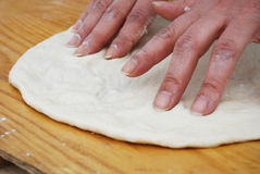 Knead and streach pizza. Hands and fingers that knead and streach pizza Stock Image