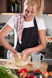 Kneading the dough. Pretty blond woman kneading the dough in the kitchen Royalty Free Stock Photos
