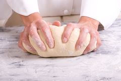 Kneading dough. Assertive tight shot of a Baker's hands kneading bread dough on a flour dusted marble cold table Stock Images