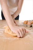 Kneading pasta dough. A young woman kneads pasta dough by hand against white background Royalty Free Stock Photo