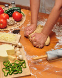 Kneading Pizza dough. Woman kneading whole-wheat pizza dough on a wooden table with flour, ingredients and utensils Stock Images