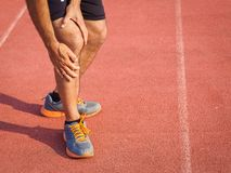 Knee Injuries. sport man with strong athletic legs holding knee. With his hands in pain after suffering muscle injury during a running workout training on Royalty Free Stock Photography