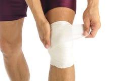 Knee injury. Male athlete wraps knee injury with bandage Royalty Free Stock Image