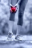 Knee injury - runner with sprained leg joint pain. Closeup of female athlete's leg with red circle showing pain. Woman holding with hands around hurting knee stock image