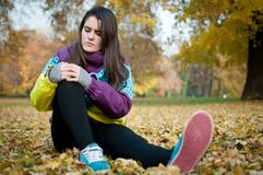 Knee injury - woman sitting in pain. Outdoor in nature Stock Photos