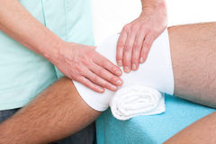 Knee joint massage. Physiotherapist making a massage of injured patient's knee joint Royalty Free Stock Photos