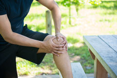 Knee joint pain outside. Closeup cropped portrait, man in black shirt and shorts holding knee in severe pain, isolated trees and picnic bench outside background Royalty Free Stock Photography