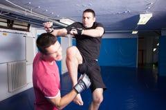 Knee kick during mma training Stock Photo
