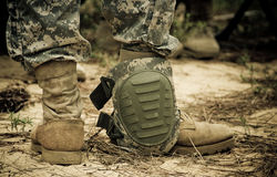 Knee pad. Resting on the ankle of a US Army soldier during a briefing Stock Image
