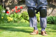 Knee pads worn by elderly senior old man in garden stock images
