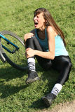 Knee pain. Female bike rider takes a tumble, holding her knee from pain Royalty Free Stock Photography