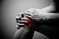 Knee pain. Young woman having knee pain stock image