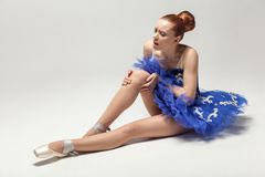 Knee pain. ballerina with bun collected hair wearing blue dress. And pointe shoes holding on injured knee while sitting on white floor. indoor, studio shot stock photo