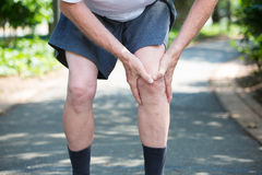 Knee pain. Closeup cropped portrait, older man in white shirt, gray shorts, standing on paved road, in severe knee pain, isolated trees outside outdoors Stock Photography
