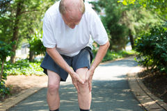 Knee pain. Closeup portrait, older man in white shirt, gray shorts, standing on paved road, in severe knee pain, isolated trees outside outdoors background Royalty Free Stock Photo