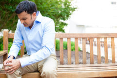 Knee pain. Closeup portrait, young handsome man in blue shirt, brown khakis, sitting on wooden bench in severe knee pain, isolated trees outside background Stock Photography