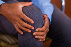 Knee pain on a man, both hands holding it and making some massage.  Stock Image