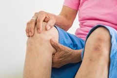 Knee pain in old women stock photography