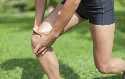 Knee pain during sports activity. Woman has an injury and holding her knee Royalty Free Stock Photo