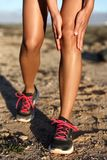 Knee pain trail running race injury runner woman. Runner woman gripping painful hurt knee pain. Athlete woman running outside with body injury. Closeup of royalty free stock images