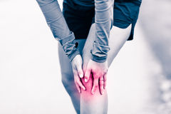 Knee pain, woman holding sore and painful leg. Runners knee leg pain, woman holding sore and overtrained painful knee, sprain or cramp ache filled with red pink Stock Image