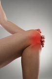 Knee pain. Woman touching her knee in pain. Gout or arthritis concept Stock Photography