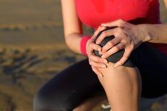 Knee runner injury. Runner sport knee injury. Woman in pain while running in beach. Caucasian female athlete with painful kneecap Royalty Free Stock Photo