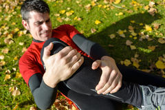 Knee sport injury. Male athlete lying on the ground and suffering a tibia fracture. Grabbing his painful leg with two hands Stock Photography