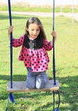 Kneeing girl on swing Royalty Free Stock Photo