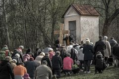 Kneeing people in front of the cross. RUZOMBEROK, SLOVAKIA - APRIL 14: Kneeing people in front of the cross during easter at calvary on April 14, 2019 in royalty free stock photo