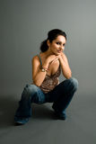 The kneel. A young attractive hispanic female crouches down for a pose Stock Photo