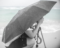 Kneel in Rain by the Sea Stock Photo