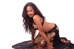 Kneeling belly dancer in gold and brown outfit Royalty Free Stock Images