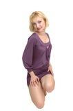 Kneeling blond lady in purple dress 14. An friendly blond girl in an short tight purple dress standing in an studio Stock Photo