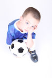 Kneeling boy with soccer ball. And hand on face Royalty Free Stock Photography