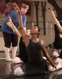 Kneeling Dance Students. Ballet class teacher helps students practice dance moves stock photography