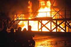 Kneeling firefighters in front of burning structure during firefighting exercise Stock Image