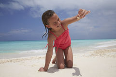 Kneeling girl showing a crab shes collected on the beach Royalty Free Stock Image