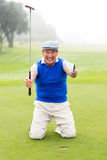 Kneeling golfer cheering on putting green Stock Images