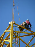 Kneeling High. Construction worker kneeling on a scaffold high above the ground setting the hooks from a crane Stock Photo