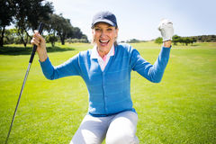 Kneeling lady golfer cheering on putting green Royalty Free Stock Images