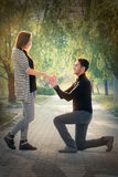 Kneeling Man Proposing with an Engagement Ring. Man proposing marriage with a romantic gesture Royalty Free Stock Image