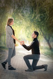 Kneeling Man Proposing with an Engagement Ring Royalty Free Stock Photo
