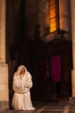 Kneeling monk in dark church Stock Image