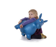 Kneeling near plastic donkey young girl Royalty Free Stock Photo